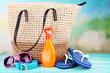 Leinwandbild Motiv Summer wicker bag with accessories on nature background