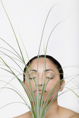 Indian woman holding grass in front of face