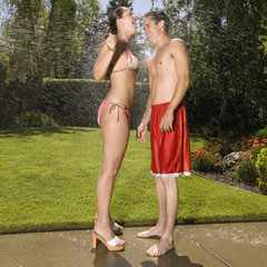 Hispanic couple standing in sprinkler