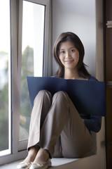 Asian businesswoman reading in window