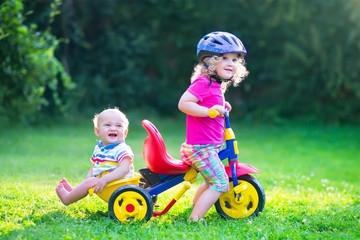 Two kids on a bike in the garden