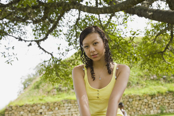Hispanic teenaged girl under tree