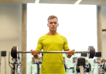 man doing exercise with barbell in gym