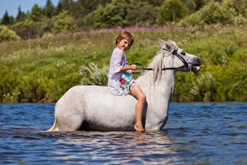 Girl riding a horse in a river