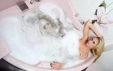 Woman blonde in a bath  with foam