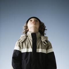 Hispanic boy in jacket looking up