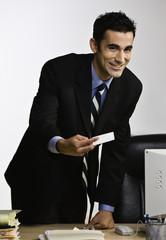 Indian businessman handing business card over desk