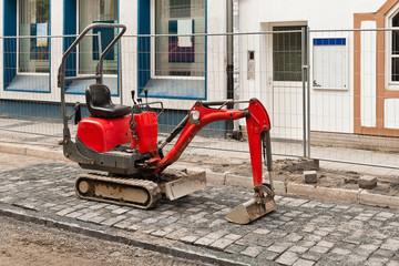 Ein roter Minibagger steht auf neu verlegtem Strassenpflaster