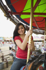Mixed Race teenaged girl on carousel horse