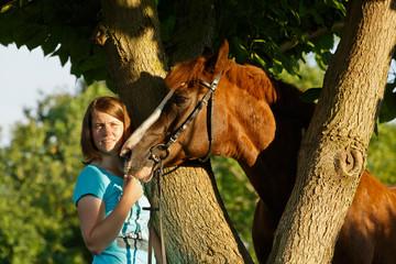 Frau mit Pferd am Baum
