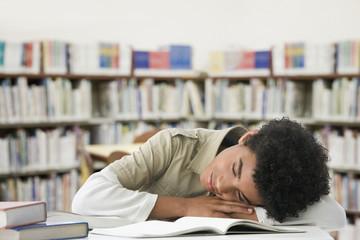 Hispanic boy sleeping in library