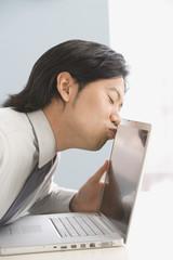 Asian businessman kissing laptop