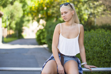 Thoughtful and sad young girl sitting outdoor
