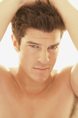 Bare-chested man with hands in hair