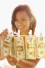 Asian woman hanging money on clothes line