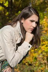 Portrait: Traurige junge Frau im Herbst lehnt an einer Brücke