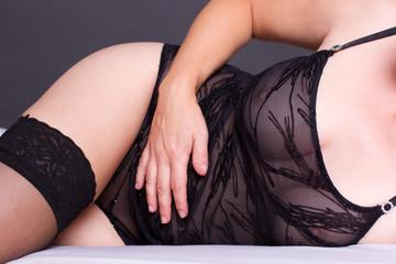 attraktive Frau in schwarzen Dessous liegt auf dem Bett
