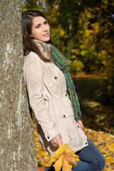 Herbst: glückliche junge Frau lehnt an einem Baum
