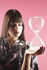 Middle Eastern woman holding hourglass