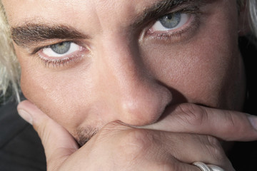 Close up of Hispanic man with hand on face