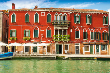 Typical Venetian canals with boats moored at a residential house