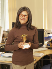 Asian businesswoman holding trophy
