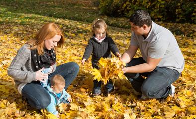 Glückliche junge Familie mit zwei Kindern im Herbst