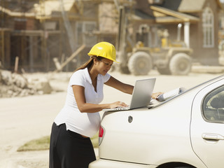Pregnant Asian businesswoman with laptop at construction site