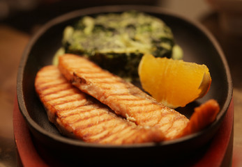salmon steak served with spinach