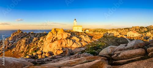 Leinwanddruck Bild Rocky ocean coastline panorama with lighthouse at sunset