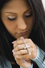 Hispanic woman holding rosary beads