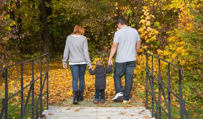 Glückliche junge Familie im Herbst beim Spazierengehen
