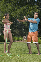 Multi-ethnic couple playing with hose
