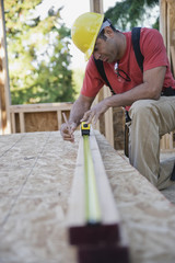 Mixed Race male construction worker measuring wood