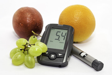 Apple, grapes, orange and glucometer