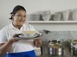 Hispanic waitress holding bowl of soup