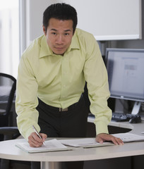 Asian businessman writing at desk