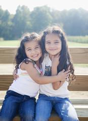 Hispanic sisters hugging on bench