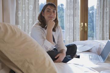 Hispanic woman sitting on bed next to laptop
