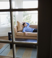 Hispanic businessman laying on sofa