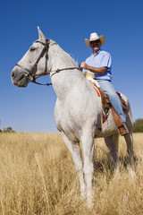 Hispanic man riding horse