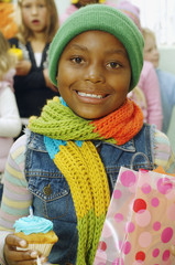 African girl holding cupcake and gift bag