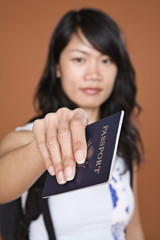 Asian woman holding out passport