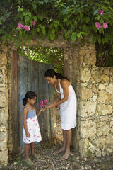 Hispanic mother giving flowers to daughter