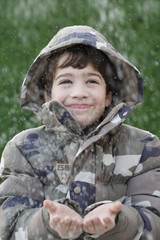 Hispanic boy with hands out in snow