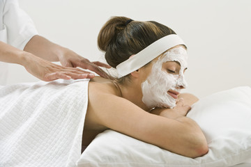 Woman receiving spa facial treatment and massage