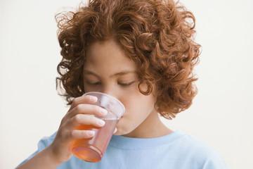 Mixed Race boy drinking juice