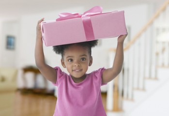 Mixed Race girl holding gift on head