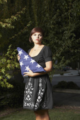 Mixed Race woman holding folded American flag