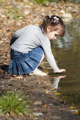 Девочка играет с отражением руки в озере